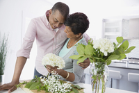 Man embracing woman as she arranges flowers in kitchen 11096026375| 写真素材・ストックフォト・画像・イラスト素材|アマナイメージズ