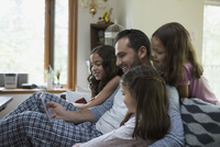 Father and daughters watching video on digital tablet on living room sofa