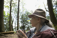 Pensive senior woman drinking coffee and looking away in woods 11096030167| 写真素材・ストックフォト・画像・イラスト素材|アマナイメージズ