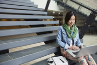 Female student using laptop while sitting on steps at college campus 11096031039| 写真素材・ストックフォト・画像・イラスト素材|アマナイメージズ