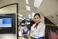 Portrait of flight attendant standing with arms crossed in airplane 11096033760| 写真素材・ストックフォト・画像・イラスト素材|アマナイメージズ
