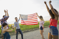 Young woman photographing friends holding American flag outdoors 11096036347| 写真素材・ストックフォト・画像・イラスト素材|アマナイメージズ