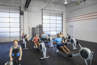 Group using rowing machine in gym
