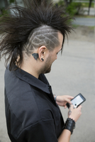 Cool man with shaved head and mohawk texting with cell phone 11096042726| 写真素材・ストックフォト・画像・イラスト素材|アマナイメージズ