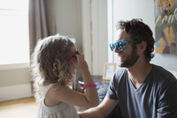 Father and daughter wearing colorful sunglasses