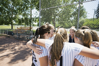 Coach and middle school girl softball team in huddle on baseball diamond