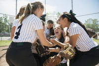 Enthusiastic middle school girl softball team celebrating
