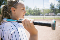 Smiling middle school girl softball player holding bat looking away