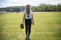 Middle school girl softball player walking in sunny outfield