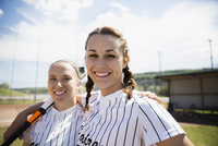 Portrait smiling middle school girl softball players hugging