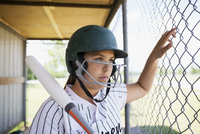 Serious middle school girl softball player wearing batting helmet and holding bat in dugout