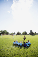 Coach talking to middle school girl soccer team on sunny field