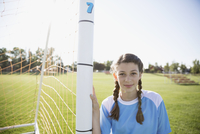 Portrait confident middle school girl soccer player leaning on goal net post