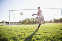 Middle school girl soccer goalie kicking the ball on sunny field