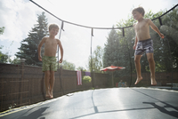 Bare chested boys jumping on trampoline in sunny backyard