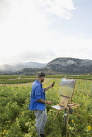 Male painter with camera phone painting in rural sunflower field 11096046074| 写真素材・ストックフォト・画像・イラスト素材|アマナイメージズ
