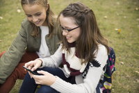 Tween girls texting with cell phone in park 11096046465| 写真素材・ストックフォト・画像・イラスト素材|アマナイメージズ