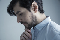 Profile portrait serious, pensive brunette Caucasian man with beard looking down with hand on chin