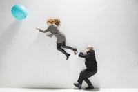 Businessman pulling leg of businesswoman holding blue balloon against white background
