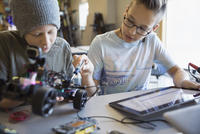 Pre-adolescent boys assembling and programming robotics at digital tablet in classroom 11096049261| 写真素材・ストックフォト・画像・イラスト素材|アマナイメージズ