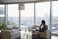Businessman with suitcase waiting in highrise lounge, looking at view 11096049602| 写真素材・ストックフォト・画像・イラスト素材|アマナイメージズ