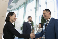 Business people handshaking, networking at conference 11096049664| 写真素材・ストックフォト・画像・イラスト素材|アマナイメージズ