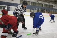 Referee dropping puck for boy ice hockey players at face off on ice hockey rink