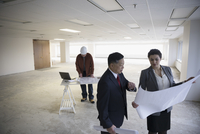 Architects reviewing blueprints in unfinished, empty open plan office 11096051033| 写真素材・ストックフォト・画像・イラスト素材|アマナイメージズ