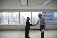 Contractor and businessman shaking hands in unfinished, empty highrise open plan office 11096051044| 写真素材・ストックフォト・画像・イラスト素材|アマナイメージズ
