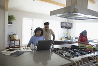 African American teenage son watching mother working at laptop in kitchen 11096051662| 写真素材・ストックフォト・画像・イラスト素材|アマナイメージズ