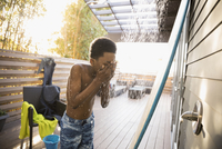 African American boy in swim trunks using beach house shower on deck