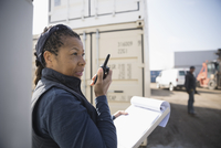 Female African American foreman with clipboard using walkie-talkie in industrial container yard 11096052678| 写真素材・ストックフォト・画像・イラスト素材|アマナイメージズ