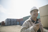 Smiling Caucasian foreman with walkie-talkie in sunny industrial container yard 11096052688| 写真素材・ストックフォト・画像・イラスト素材|アマナイメージズ