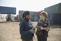 Female workers with clipboard and walkie-talkie talking in industrial container yard 11096052689| 写真素材・ストックフォト・画像・イラスト素材|アマナイメージズ