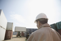 Foreman in hard-hat walking in sunny industrial container yard 11096052692| 写真素材・ストックフォト・画像・イラスト素材|アマナイメージズ