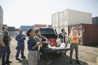 Workers at truck looking away in sunny industrial container yard 11096052713| 写真素材・ストックフォト・画像・イラスト素材|アマナイメージズ
