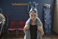 Portrait serious girl swimmer with towel around neck in locker room