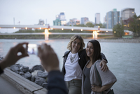 Women friends posing for photograph at urban river waterfront at dusk 11096053587| 写真素材・ストックフォト・画像・イラスト素材|アマナイメージズ
