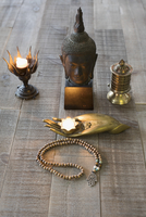 Still life of Buddha statue, candles and Mala beads altar