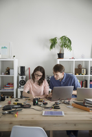 Father and teenage daughter assembling electronics at laptop at dining table 11096054155| 写真素材・ストックフォト・画像・イラスト素材|アマナイメージズ