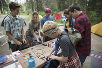 Students packing equipment in backpacks at outdoor school campsite picnic table 11096054708| 写真素材・ストックフォト・画像・イラスト素材|アマナイメージズ