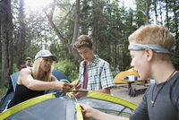 Female teacher showing teenage outdoor school boy students how to pitch a tent at campsite 11096054731| 写真素材・ストックフォト・画像・イラスト素材|アマナイメージズ