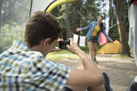 Teenage boy with camera phone photographing girl outside tent at outdoor school campsite 11096054848| 写真素材・ストックフォト・画像・イラスト素材|アマナイメージズ