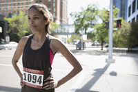 Serious, determined female marathon runner standing with hands on hips on sunny urban street 11096055245| 写真素材・ストックフォト・画像・イラスト素材|アマナイメージズ