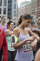 Female marathon runner checking smart watch, waiting at starting line on urban street 11096055252| 写真素材・ストックフォト・画像・イラスト素材|アマナイメージズ