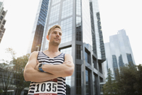 Portrait confident male marathon runner in striped tank top standing below urban highrise building 11096055388| 写真素材・ストックフォト・画像・イラスト素材|アマナイメージズ