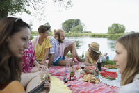 Friends and family relaxing, enjoying summer picnic at lakeside 11096055533| 写真素材・ストックフォト・画像・イラスト素材|アマナイメージズ
