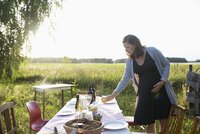 Pregnant woman setting the table for garden party dinner in sunny summer rural yard 11096055684| 写真素材・ストックフォト・画像・イラスト素材|アマナイメージズ