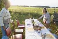 Mother and daughter setting the table for garden party dinner in rural summer yard 11096055687| 写真素材・ストックフォト・画像・イラスト素材|アマナイメージズ