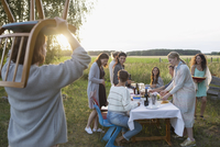 Friends setting the table and carrying chair for garden party dinner in rural summer yard 11096055689| 写真素材・ストックフォト・画像・イラスト素材|アマナイメージズ